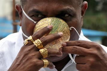 Un Indien porte un masque en or pour se protéger du coronavirus)