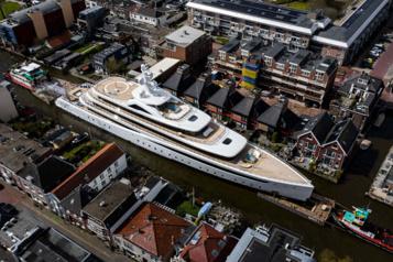 Un grand yacht de luxe se faufile dans les étroits canaux des Pays-Bas)