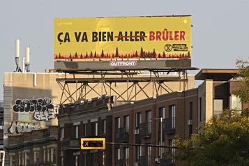 Des membres d'Extinction Rébellion modifient un panneau publicitaire à Montréal)