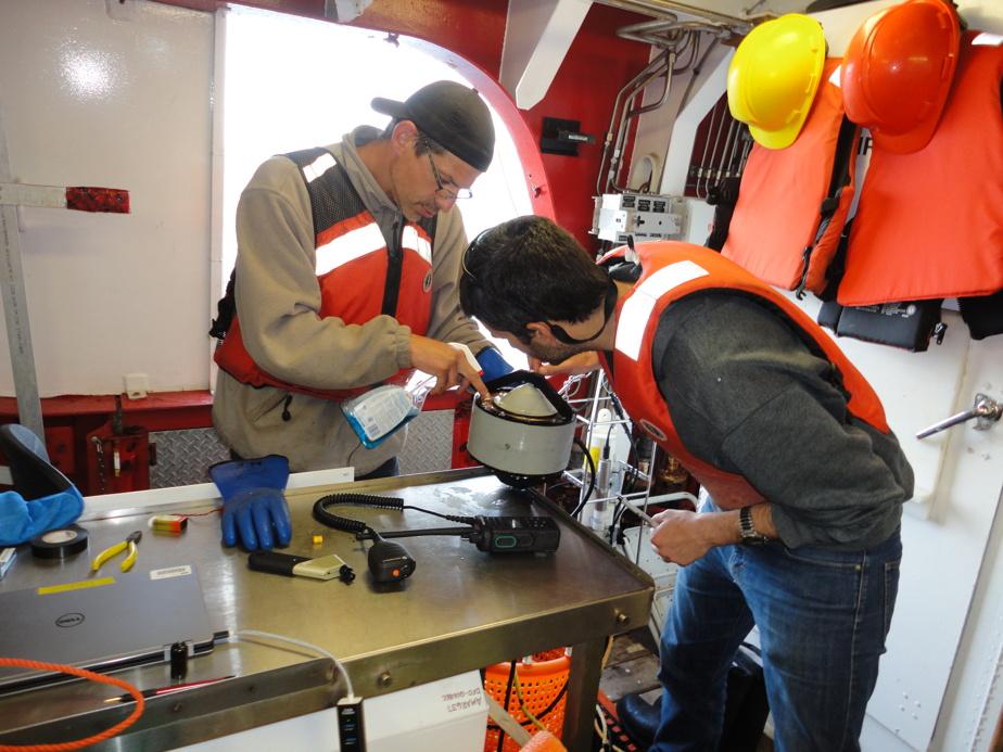 Préparation d'un émetteur acoustique basse fréquence par l'équipe de l'Institut Maurice-Lamontagne (Michel Rousseau, à gauche, et Florian Aulanier)