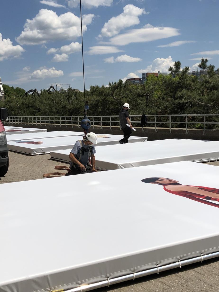 Des techniciens préparent la pose des photographies.