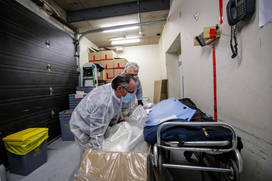 Après l'identification formelle, Sylvain Allan et Michel Degagné déplacent la dépouille dans une boîte de carton.