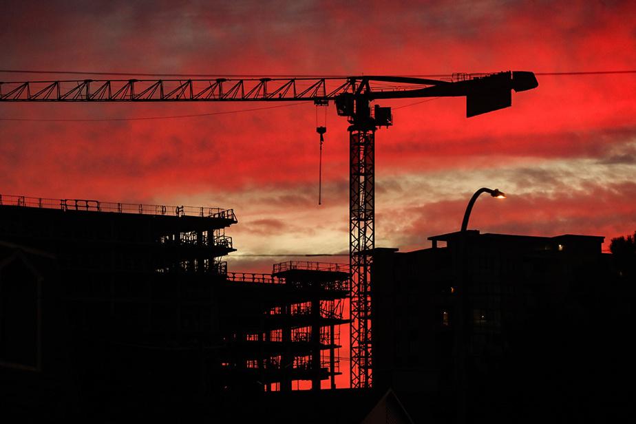 Une grue sur un chantier s'élève au-dessus d'un immeuble en construction tandis que le ciel vire au rouge en fin de journée.