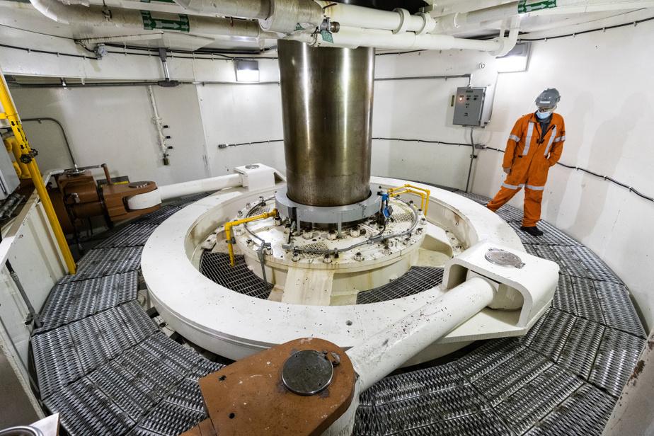 Steve Gagnon inspecte l'intérieur du puits de turbine. L'eau passe directement dans la turbine, qui produit l'électricité par l'alternateur au-dessus du puits.