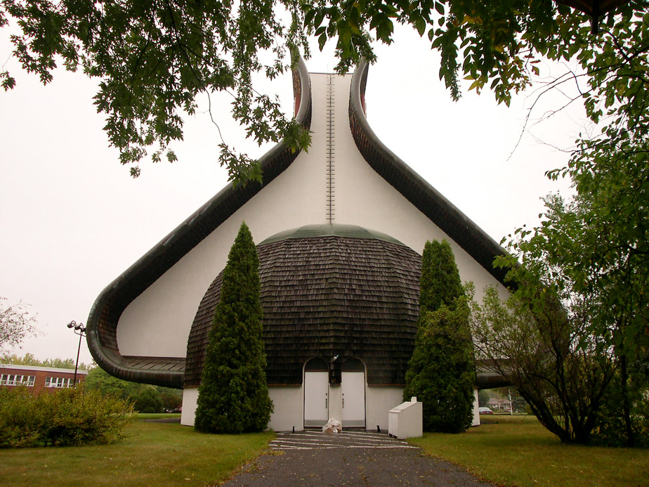 Notre-Dame-des-Champs (Repentigny) — Suivant les plans de l'architecte Roger D'Astous et de Jean-Paul Pothier, ce monument tout en courbes et en contre-courbes, construit en 1962, porte une toiture en bardeau de cèdre et affiche des angles marqués.