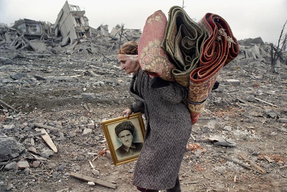Tchétchénie, février2000. «Je suis allé à Grozny cinq fois lors de la première guerre, en 1995-1996, mais je ne reconnais pas la place Minutka, la grande porte d'entrée sud de la capitale. Tout a été rasé», explique Éric Bouvet, dans un texte de Visa pour l'image. «Je viens d'arriver, c'est ma première image. Cette femme a été chassée de chez elle par les Russes, qui dynamitent tous les immeubles de peur que les combattants tchétchènes reviennent s'y cacher. Son mari et ses deux fils sont morts; il ne lui reste que le portrait de son mari et deuxtapis.»