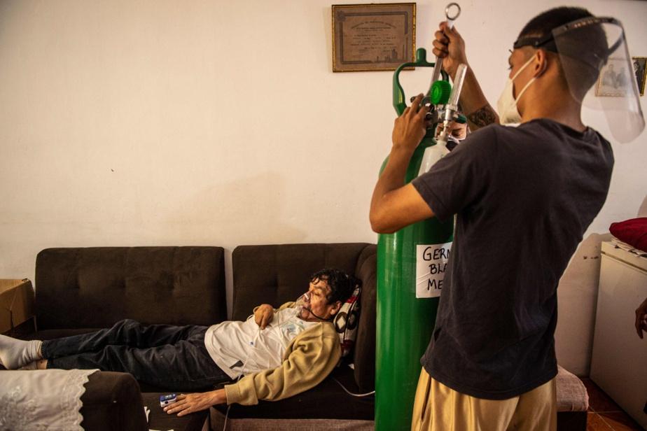 À Callao, au Pérou, German Blanco, 60ans, est allongé dans son salon alors qu'il est atteint de la COVID-19. Un proche vérifie la bonbonne d'oxygène qui l'aide à respirer.