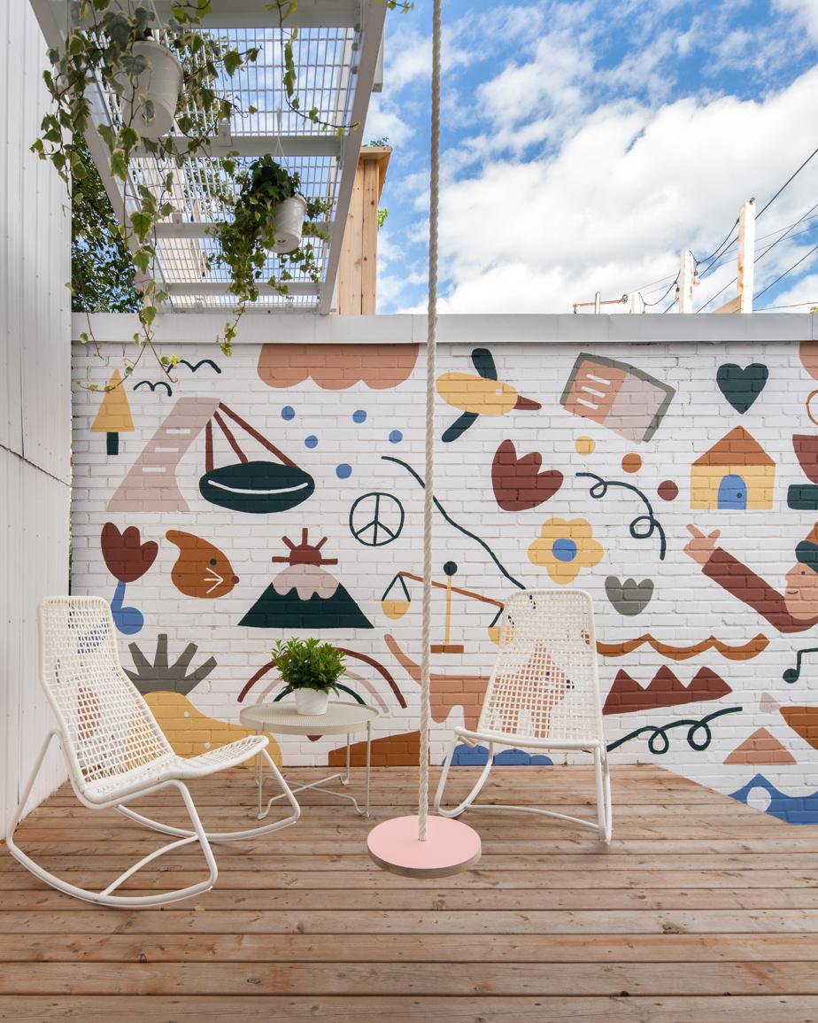 Les propriétaires ont fait appel à l'artiste Marc-Olivier Lamothe pour égayer le mur de leur garage avec une œuvre murale qui intègre des éléments représentant leur parcours et leurs intérêts.