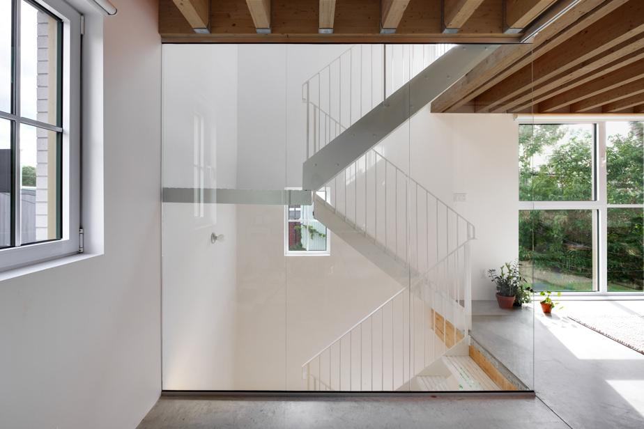 Une cloison de verre sépare le bureau de l'escalier, à côté du séjour.