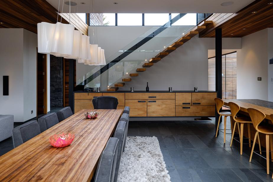 La table, qui peut accommoder 10personnes, est assise au milieu du rez-de-chaussée. Le bois de la surface est le même que celui des plans de travail de la cuisine. Comme ailleurs, les pièces ont été fabriquées sur mesure.