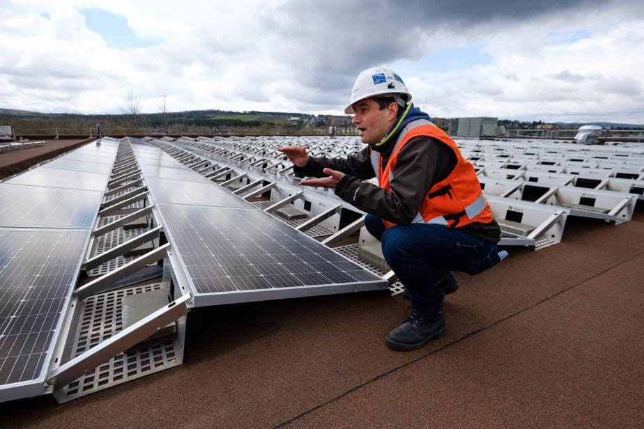 L'ingénieur Simone Soldati explique le fonctionnement du microréseau à côté des panneaux solaires sur le toit du centre sportif.