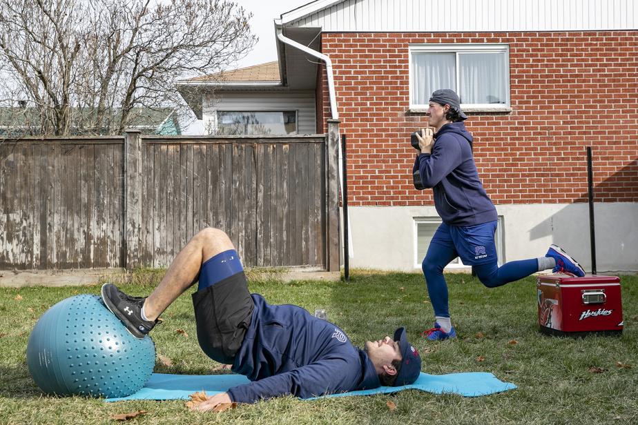 Avec la fermeture des gyms en zone rouge, Joël Teasdale (au sol) et Rafaël Harvey-Pinard s'entraînent avec les moyens du bord dans la cour arrière de Teasdale, à Blainville.