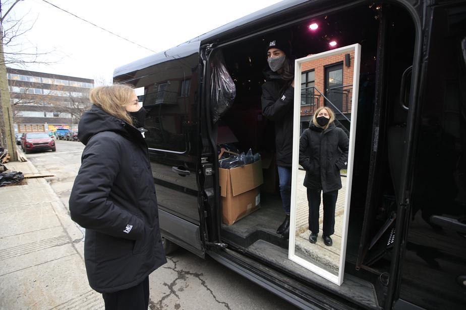 Catherine Gauthier tient un miroir afin que Frédérique DuSault puisse se voir avec son nouveau manteau.