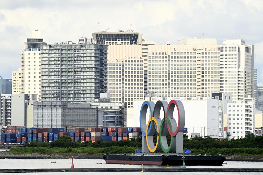 Les anneaux olympiques, avec le port et des édifices à l'arrière-plan.