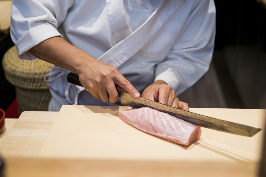Assis au bar, on admire la technique irréprochable du chef… et ses couteaux très affûtés!