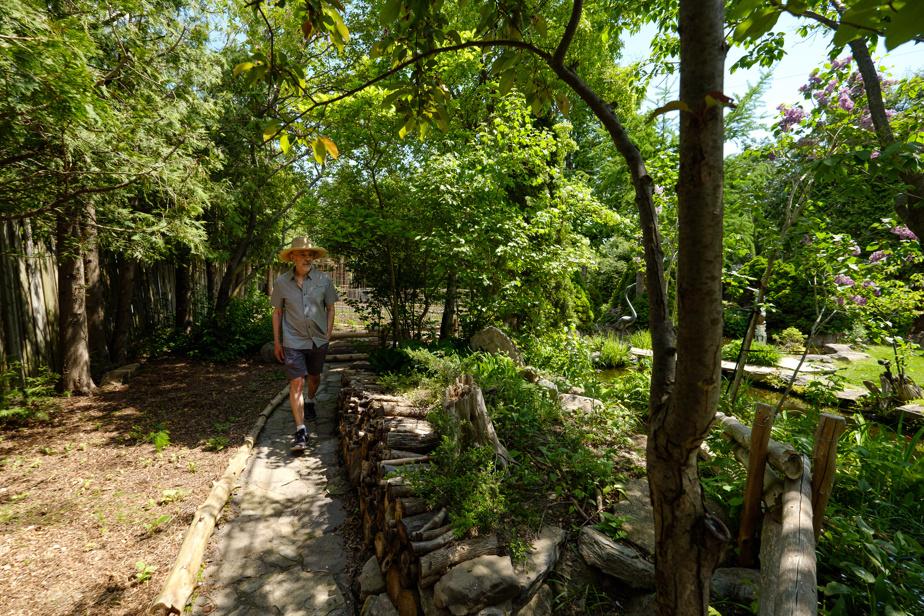 Jean Bazinet marche dans un des sentiers qu'il a aménagés, bordant l'étang.