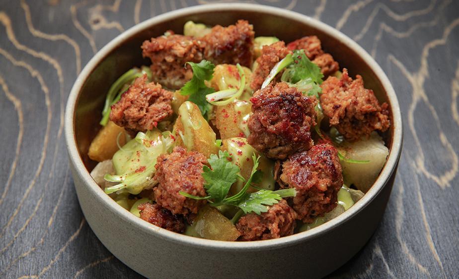 Le chef Daniel Silva propose plusieurs versions du salchipapas, un plat très répandu au Pérou, mélange de saucisses et de pommes de terre jaunes péruviennes frites, ici en version classique avec aïoli vert.