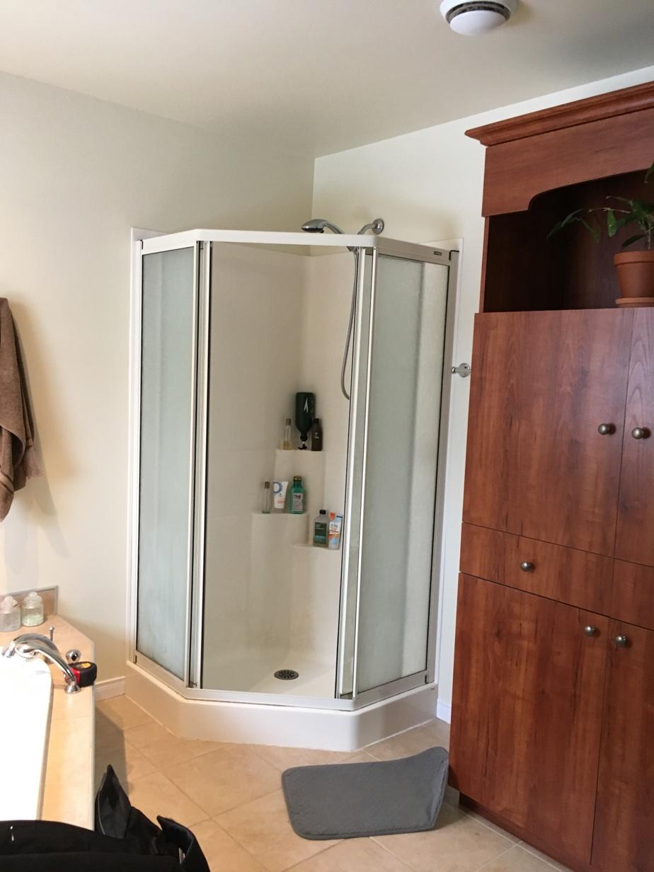 Dans l'ancienne salle de bains, une volumineuse penderie, une imposante baignoire en coin et une douche en coin en acrylique faisaient paraître la pièce très petite.