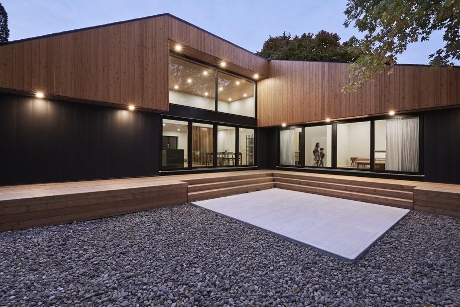 L'été, la cour est une pièce supplémentaire où la famille prend notamment ses repas. Les trottoirs de bois permettent de passer d'une partie à l'autre de la maison par l'extérieur.