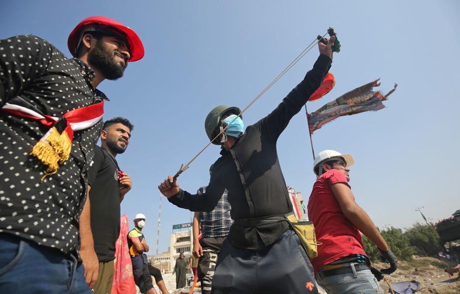 AFP              Des manifestants utilisent des lance-pierres contre la police près de la Zone verte à Bagdad