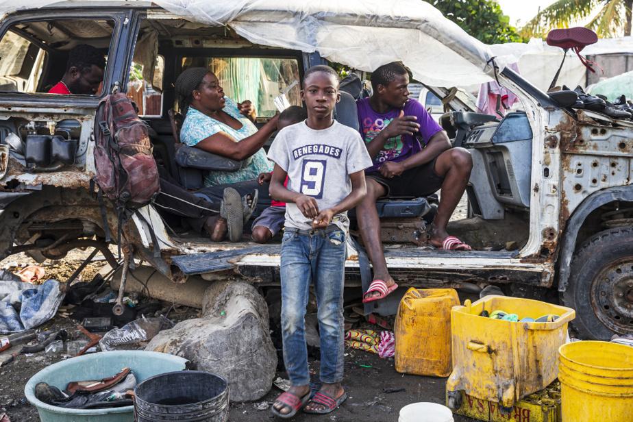 Une femme a établi son commerce dans la carcasse d'une voiture, sur la berge de la rivière, dans le bidonville de Barrière Bouteille. Elle y vend des souliers pour subvenir aux besoins de sa famille.