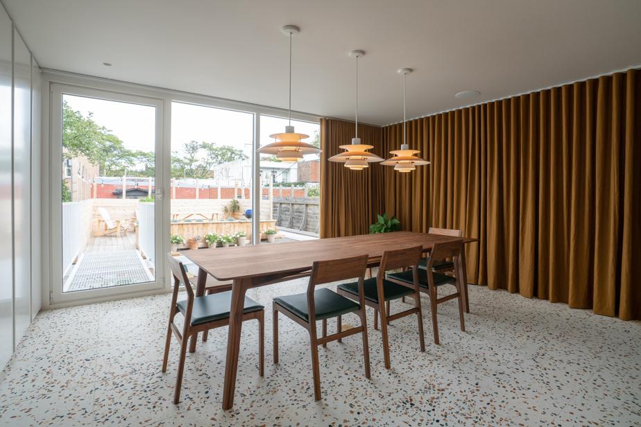 Un ensemble fabriqué par Kastella et des lampes PH5 de l'entreprise danoise Louis Poulsen agrémentent la salle à manger.