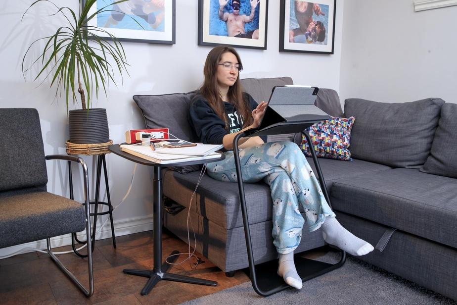 Mathilde aime bien étudier confortablement assise sur le sofa. Cette table à ordinateur portable, offerte par l'entremise de l'entreprise Aura, lui permet de s'installer à peu près n'importe où.