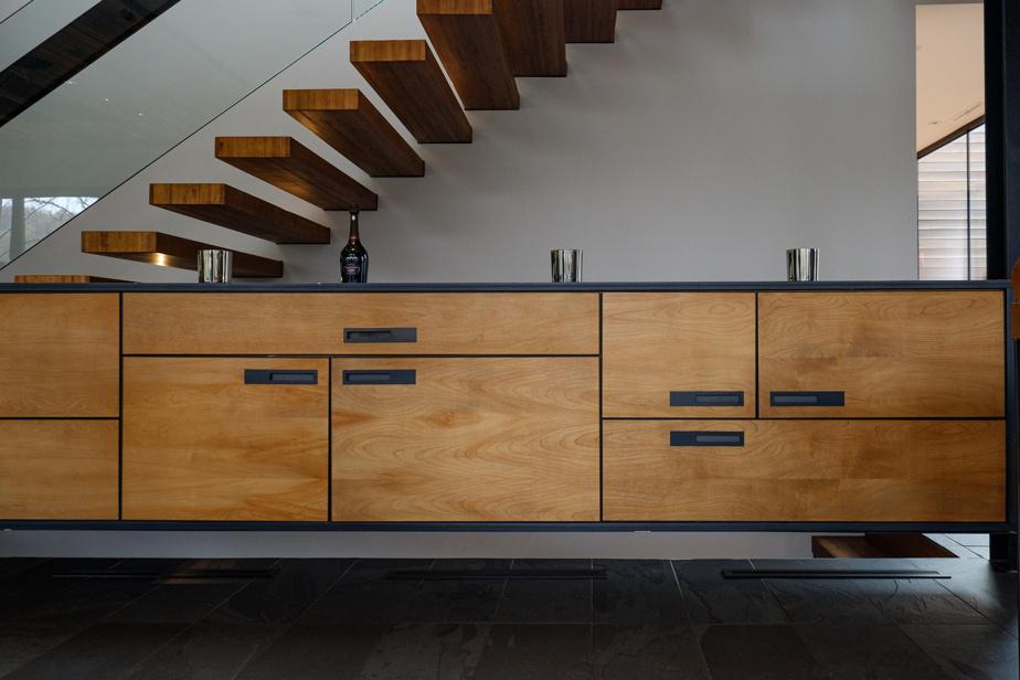 L'escalier a représenté un casse-tête. Les marches aériennes sont retenues au mur d'un seul côté. L'ancrage a dû être réajusté plusieurs fois. Qu'à cela ne tienne, le propriétaire a dessiné un très long meuble également suspendu sous les marches!