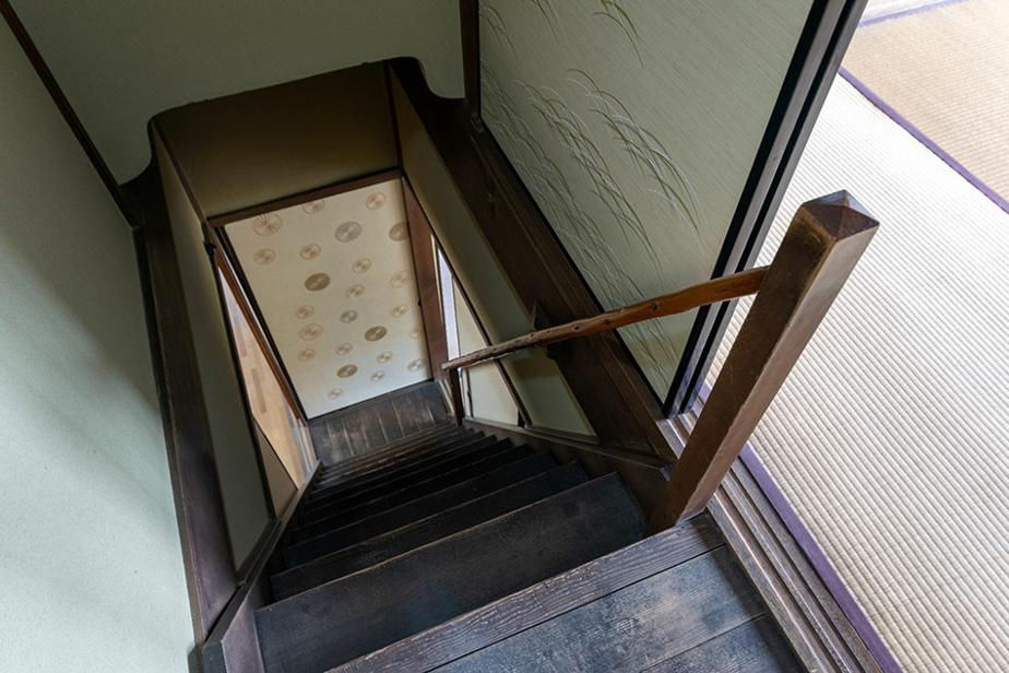 L'escalier, dont le sommet est entouré d'un fusuma, présente une patine obtenue par le passage des années.