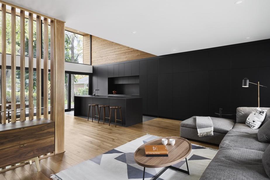Une paroi de bois ajourée délimite le salon de l'espace cuisine et salle à manger. À l'arrière de la maison, les hautes fenêtres permettent de profiter de beaucoup de lumière et d'admirer le jardin.