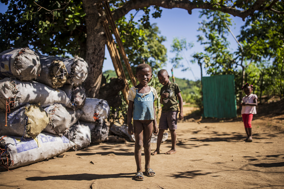 Des enfants prennent la pose devant des sacs de charbon dans le village d'Acul-Samedi. Le charbon demeure massivement utilisé pour la cuisson des aliments en Haïti.