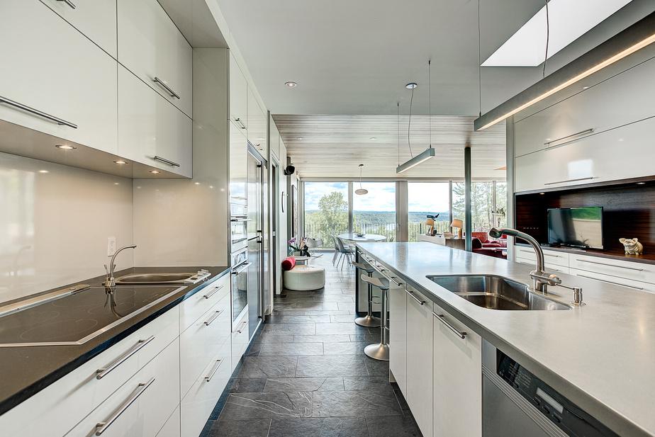 La cuisine est équipée d'électroménagers Thermador et Gaggenau, incluant des hottes rétractables. Les comptoirs en Corian et les dosserets en stratifié renforcent le style minimaliste.
