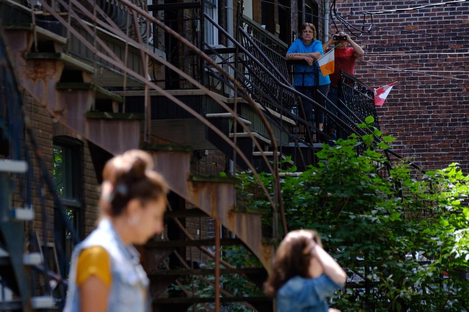 Des voisins observent la pièce de théâtre qui se déploie sur le parterre avant d'une résidence privée de Pointe-Saint-Charles.