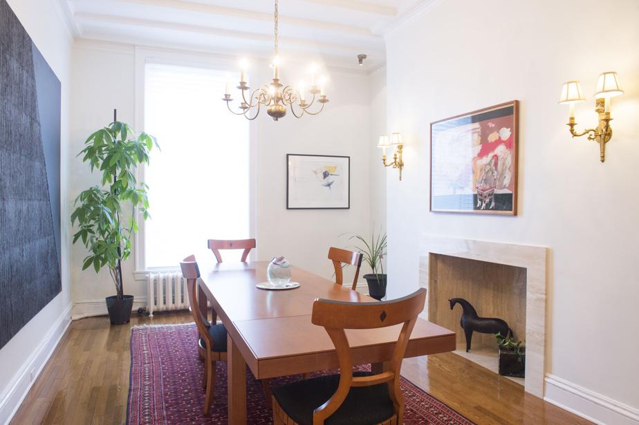 La salle à manger se trouve tout au fond du couloir, près de la cuisine. Les murs blancs présents partout dans l'appartement permettent de mettre en valeur la vaste collection d'œuvres d'art du propriétaire.
