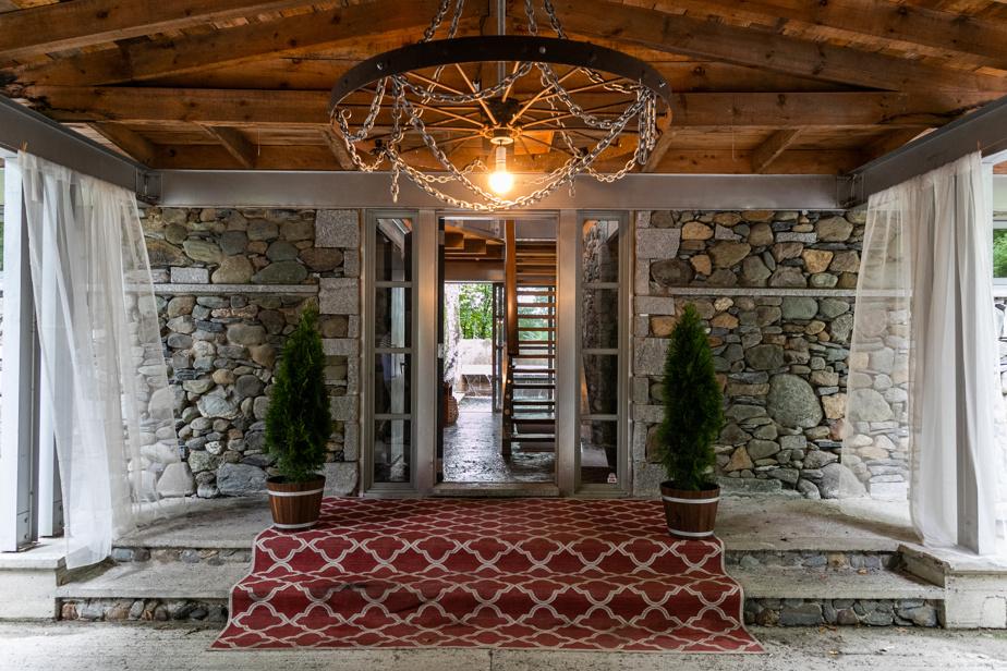 Effet majestueux sous la porte cochère grâce au tapis rouge, aux pots de conifères symétriques, à la charpente en bois brute, à la pierre naturelle et au lustre magistral