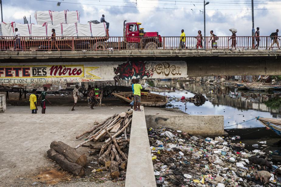 Ce pont enjambant l'embouchure de la rivière du Haut-du-Cap, à Cap-Haïtien, montre l'empiétement du bidonville de Barrière Bouteille sur l'eau, qui occupe désormais moins de la moitié de l'espace sous le tablier.