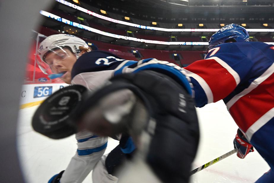 Trevor Lewis des Jets de Winnpeg et Brett Kulak du Canadiens luttent pour la rondelle lors de la 1epériode d'action au Centre Bell.