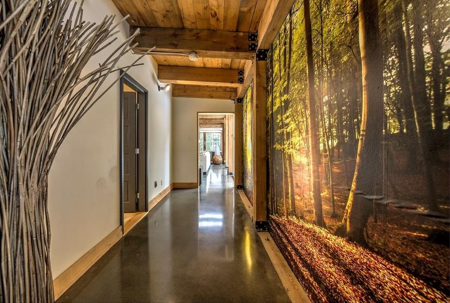 On se trouve ici au rez-de-chaussée, dans un passage qui relie le salon à une salle de bains et à une chambre principale. La murale forêt d'automne égaie avec bonheur ce mur sans fenêtres.