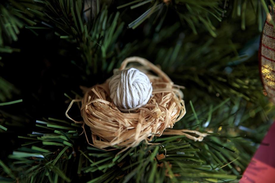 Un nid de raphia accueille un œuf fait de cordelette (en quincaillerie) enroulée autour d'une boule de papier.