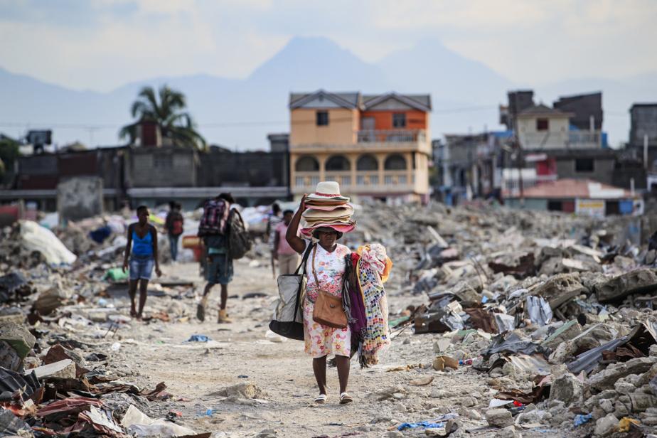 Une femme traverse les décombres du quartier ShadaII, transportant chapeaux et vêtements.