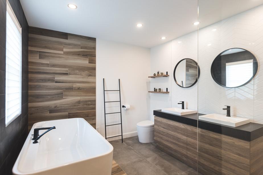 La circulation est fluide dans la nouvelle salle de bains. La douche, bordée d'une paroi de verre, est facilement accessible, tout comme la baignoire. La pièce demeure sobre, même s'il y a plusieurs textures différentes.