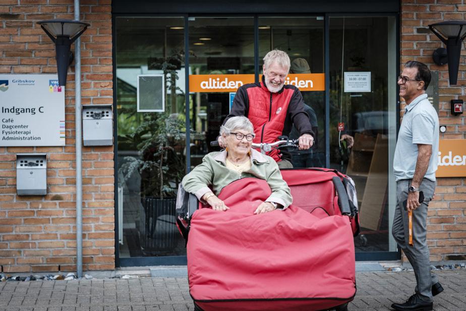Poussée par un bénévole à bicyclette, une résidente s'apprête à aller se faire promener au village. «Souvent, les gens qui font beaucoup de démence vont se rappeler plein de choses en allant visiter deslieux qu'ils connaissent», dit la directrice du centre Skovsminde, Louise Silbo Raft.
