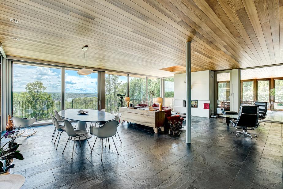 Le concept offre de nombreux points de vue de l'intérieur comme de l'extérieur. L'absence de moulures et l'effet continu des lames de bois au plafond donnent une sensation de prolongement entre les espaces. La propriétaire a fait faire un balcon abrité tout autour de la maison pour pouvoir y marcher aussi l'hiver.