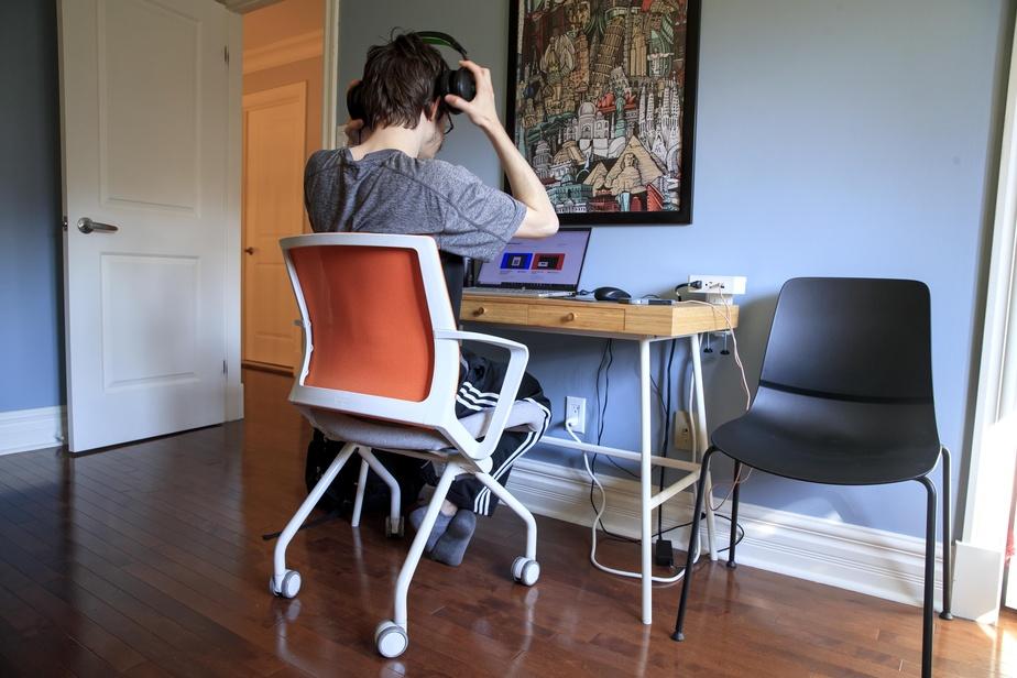 Philipe apprécie son fauteuil à roulettes d'un gabarit un peu plus léger que ce que l'on retrouve habituellement dans les bureaux. À noter, dans le coin à droite, le module d'alimentation avec prises de courant et ports USB. Celui-ci est offert par l'agence Aura, dont la salle d'exposition se trouve dans le Vieux-Montréal.