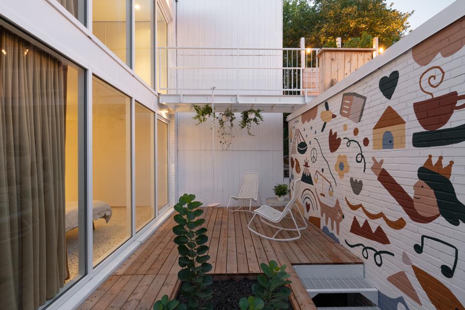 Une passerelle relie l'aire de vie de l'étage à une terrasse aménagée sur le toit du garage.