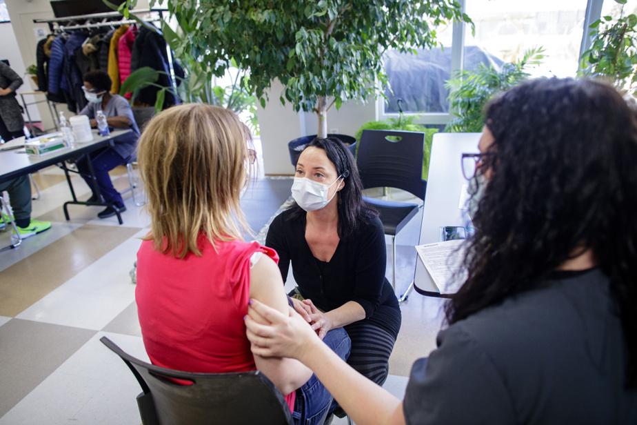 À une autre table, une jeune femme n'affiche pas le même enthousiasme. Assise sur une chaise à côté de l'infirmière auxiliaire Marie-Céline Forget, elle pleure à chaudes larmes. Elle est terrifiée à la vue de la seringue, qui contient une dose du vaccin de Pfizer-BioNTech. MmeForget (à droite) lui parle calmement pour tenter de l'apaiser. L'infirmière clinicienne Valérie Demers, assistante au supérieur immédiat pour l'équipe mobile de vaccination contre la COVID-19, vient en renfort pour aider la jeune femme, qui finit par se calmer et accepter de recevoir le vaccin. MmeForget l'applaudit quand tout est terminé.