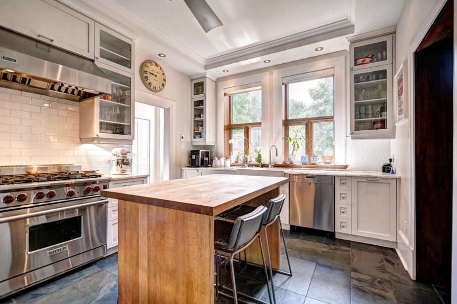 La cuisine, dotée d'une cuisinière au gaz à six ronds, de nombreux rangements et d'une table centrale en chêne en guise d'îlot, est conçue pour préparer les repas efficacement à plusieurs. Les matériaux choisis (plancher en ardoise et comptoirs en marbre) s'harmonisent bien avec le style de la maison.