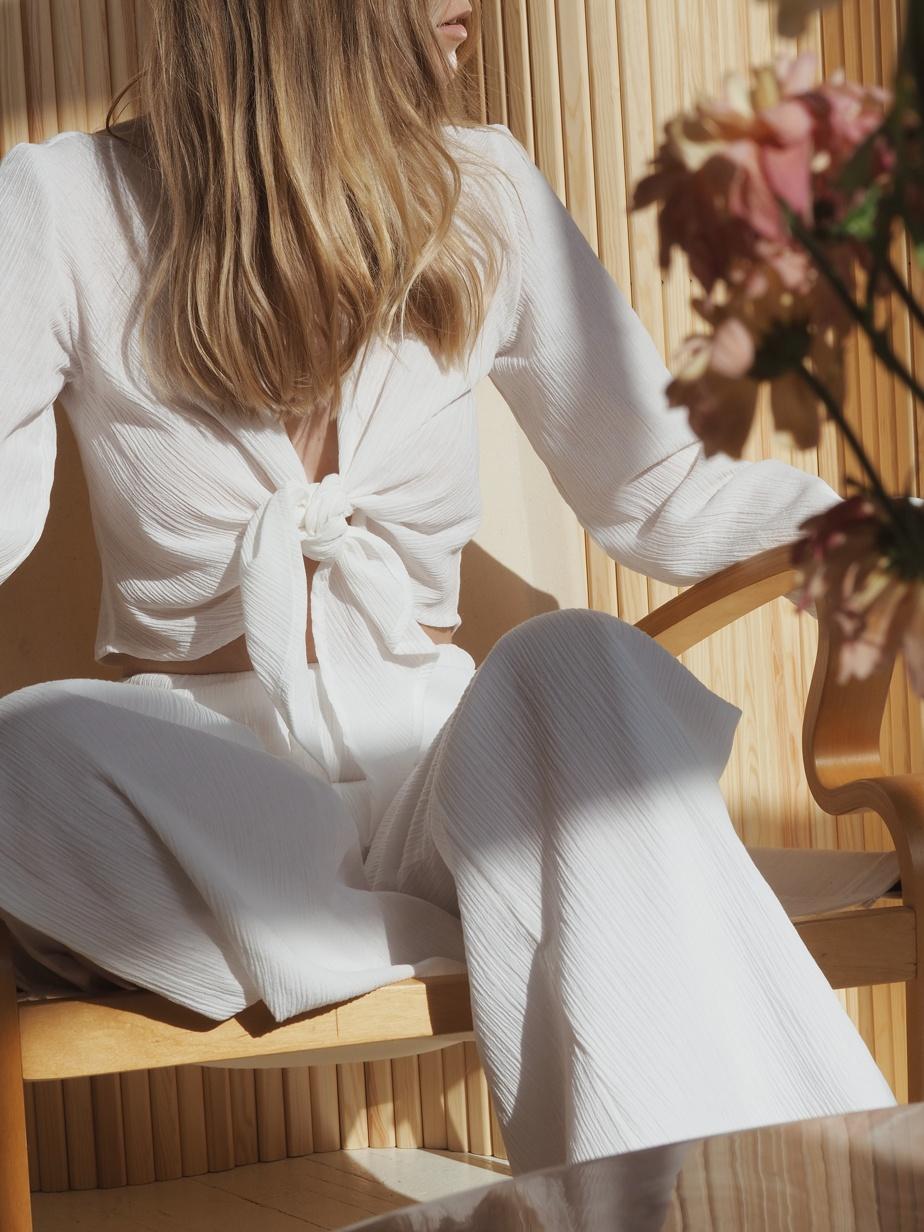 Le pantalon à la jambe ample et fendue (109,99$) se porte bien avec le haut noué (69,99$), autre pièce de la gamme Mila.