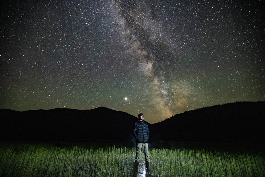 Photographe de brousse: le photographe Éric Deschamps les pieds dans l'eau d'un lac en altitude situé dans les monts Chic-Chocs, en Gaspésie, avec la Voie lactée pour toile de fond.