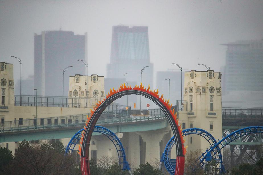 Vue de Montréal en trois temps: un manège coloré de La Ronde au premier plan, des tours du pont Jacques-Cartier derrière et, au loin, les édifices du centre-ville.